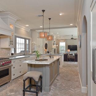 Inspiration för ett mellanstort vintage kök, med en rustik diskho, luckor med infälld panel, vita skåp, marmorbänkskiva, beige stänkskydd, rostfria vitvaror, tegelgolv och en köksö
