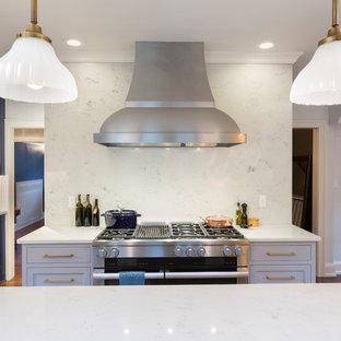 ミルウォーキーの大きいトラディショナルスタイルのおしゃれなキッチン (エプロンフロントシンク、シェーカースタイル扉のキャビネット、青いキャビネット、大理石カウンター、白いキッチンパネル、大理石の床、パネルと同色の調理設備、淡色無垢フローリング、赤い床) の写真