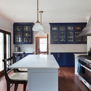 Modelo de cocina en U, clásica, grande, cerrada, con fregadero sobremueble, armarios estilo shaker, puertas de armario azules, encimera de mármol, salpicadero blanco, salpicadero de mármol, electrodomésticos con paneles, suelo de madera clara, una isla y suelo rojo