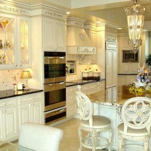 ニューヨークの大きいヴィクトリアン調のおしゃれなキッチン (アンダーカウンターシンク、レイズドパネル扉のキャビネット、白いキャビネット、御影石カウンター、ベージュキッチンパネル、石タイルのキッチンパネル、パネルと同色の調理設備、セラミックタイルの床、ベージュの床) の写真