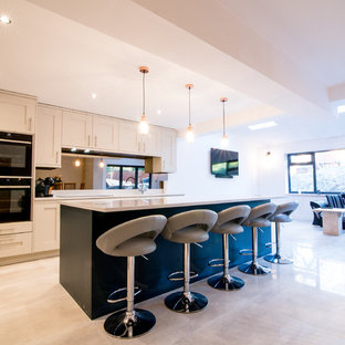 Large traditional open concept kitchen designs - Large elegant single-wall porcelain floor open concept kitchen photo in Manchester with shaker cabinets, blue cabinets, quartzite countertops, glass sheet backsplash, paneled appliances, an island and blue countertops