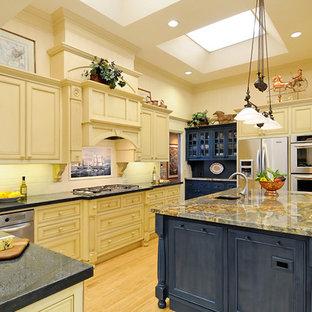 Стильный дизайн: огромная п-образная кухня в классическом стиле с обеденным столом, двойной раковиной, фасадами с декоративным кантом, белыми фасадами, столешницей из гранита, желтым фартуком, фартуком из керамической плитки, техникой из нержавеющей стали, полом из бамбука и островом - последний тренд