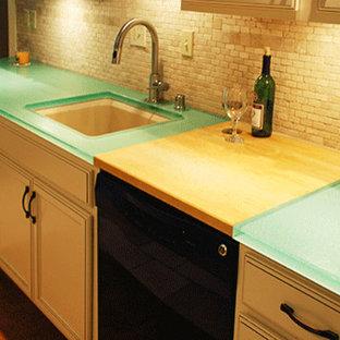 Foto på ett mellanstort vintage grön kök, med en undermonterad diskho, luckor med upphöjd panel, beige skåp, bänkskiva i glas, beige stänkskydd, stänkskydd i stenkakel och svarta vitvaror
