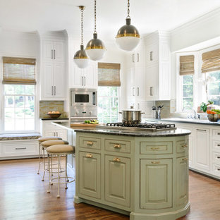 Traditional eat-in kitchen designs - Example of a classic u-shaped medium tone wood floor and brown floor eat-in kitchen design in Charlotte with white cabinets, multicolored backsplash, mosaic tile backsplash, stainless steel appliances, an island, an undermount sink, granite countertops and beaded inset cabinets