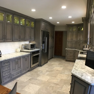 Design ideas for a mid-sized traditional kitchen in Cleveland with a farmhouse sink, raised-panel cabinets, grey cabinets, quartz benchtops, white splashback, subway tile splashback, stainless steel appliances, vinyl floors and multi-coloured floor.