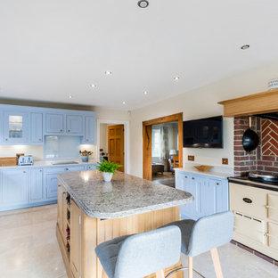Inspiration for a classic u-shaped enclosed kitchen in Surrey with shaker cabinets, blue cabinets, quartz worktops, blue splashback, an island, a belfast sink, glass sheet splashback, coloured appliances, beige floors and grey worktops.