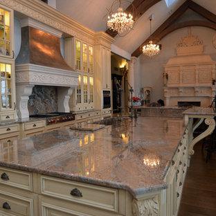 ニューヨークの大きいヴィクトリアン調のおしゃれなキッチン (アンダーカウンターシンク、ガラス扉のキャビネット、ベージュのキャビネット、御影石カウンター、グレーのキッチンパネル、石スラブのキッチンパネル、シルバーの調理設備の、濃色無垢フローリング、茶色い床) の写真