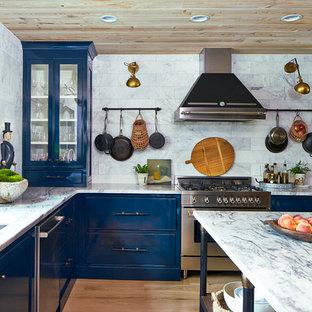 Foto di una cucina ad U classica con lavello sottopiano, ante blu, top in marmo, paraspruzzi bianco, paraspruzzi con piastrelle in pietra, elettrodomestici in acciaio inossidabile, parquet chiaro, isola e ante di vetro