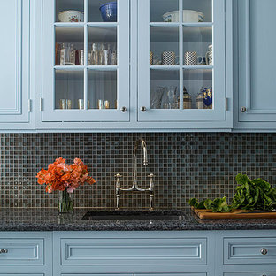 Photo of a small traditional galley kitchen in New York with an undermount sink, louvered cabinets, blue cabinets, granite benchtops, grey splashback, glass tile splashback, panelled appliances and porcelain floors.
