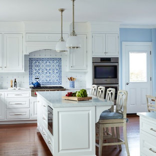 Inspiration for a large timeless u-shaped medium tone wood floor enclosed kitchen remodel in New York with an undermount sink, raised-panel cabinets, white cabinets, marble countertops, blue backsplash, ceramic backsplash, paneled appliances, an island and white countertops