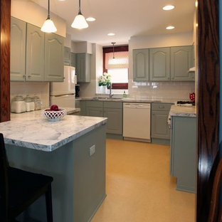 This is an example of a traditional u-shaped eat-in kitchen in Minneapolis with an integrated sink, raised-panel cabinets, grey cabinets, laminate benchtops, white splashback, subway tile splashback and white appliances.