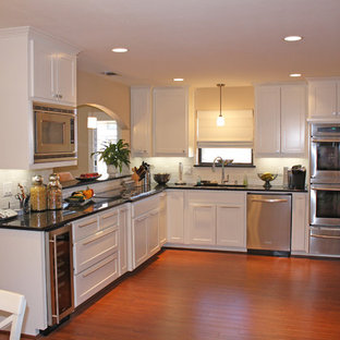 Elegant l-shaped kitchen photo in Dallas with stainless steel appliances, recessed-panel cabinets and white cabinets