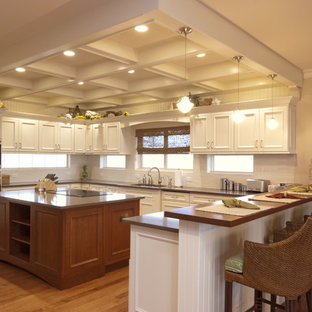 Traditional kitchen ideas - Elegant kitchen photo in New York with recessed-panel cabinets, white cabinets, white backsplash and stainless steel appliances