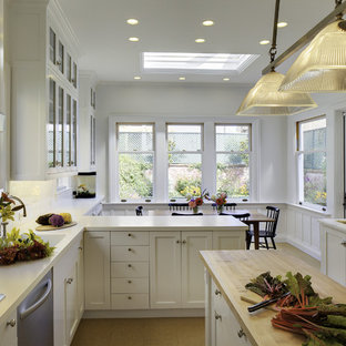 Traditional eat-in kitchen pictures - Elegant eat-in kitchen photo in San Francisco with glass-front cabinets, stainless steel appliances, solid surface countertops, white cabinets, white backsplash and subway tile backsplash