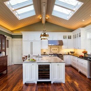Elegant l-shaped kitchen photo in Philadelphia with recessed-panel cabinets, white cabinets, beige backsplash and paneled appliances