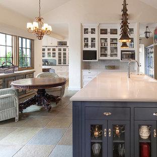 Idéer för att renovera ett mycket stort vintage svart svart skafferi, med en rustik diskho, luckor med infälld panel, vita skåp, bänkskiva i kvarts, stänkskydd i trä, skiffergolv, en köksö och grönt golv
