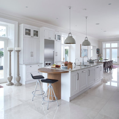 Example of a transitional eat-in kitchen design in Belfast with an undermount sink, shaker cabinets, white cabinets and an island