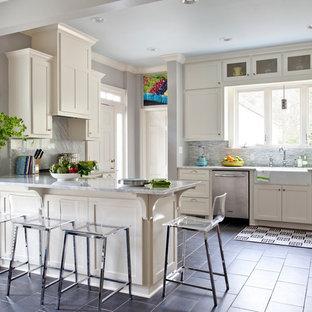 Klassisk inredning av ett kök, med rostfria vitvaror, en rustik diskho och grått golv
