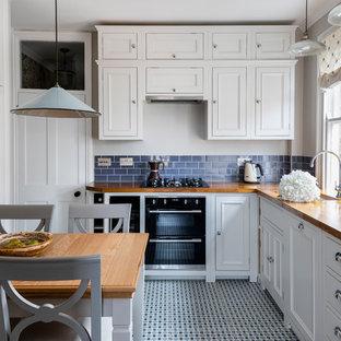 Mittelgroße Klassische Wohnküche ohne Insel in L-Form mit Landhausspüle, weißen Schränken, Arbeitsplatte aus Holz, Küchenrückwand in Blau, Rückwand aus Keramikfliesen, Elektrogeräten mit Frontblende, Keramikboden, blauem Boden, Schrankfronten mit vertiefter Füllung und brauner Arbeitsplatte in London