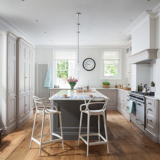 Medium sized classic l-shaped kitchen in Sussex with a belfast sink, recessed-panel cabinets, grey cabinets, stainless steel appliances, light hardwood flooring, an island and brown floors.