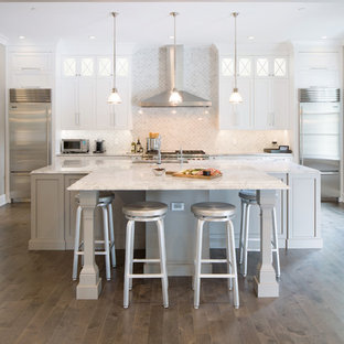 Inspiration for a large transitional galley medium tone wood floor kitchen remodel in Philadelphia with recessed-panel cabinets, white cabinets, granite countertops, white backsplash, stainless steel appliances and an island