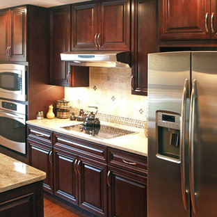 Example of a small classic galley medium tone wood floor eat-in kitchen design in Atlanta with an undermount sink, raised-panel cabinets, dark wood cabinets, granite countertops, beige backsplash, ceramic backsplash, stainless steel appliances and an island
