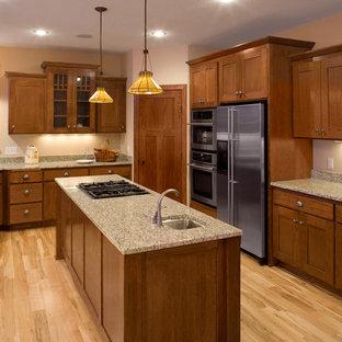 На фото: кухня в классическом стиле с фасадами в стиле шейкер, фасадами цвета дерева среднего тона и техникой из нержавеющей стали с
