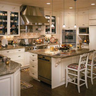 Traditional eat-in kitchen ideas - Example of a classic u-shaped dark wood floor eat-in kitchen design in Denver with an undermount sink, raised-panel cabinets, white cabinets, granite countertops, stainless steel appliances, an island, beige backsplash and ceramic backsplash