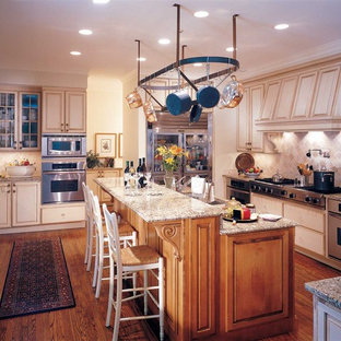 Example of a classic u-shaped medium tone wood floor kitchen pantry design in Denver with raised-panel cabinets, medium tone wood cabinets, granite countertops, stainless steel appliances, two islands, a drop-in sink, beige backsplash and stone tile backsplash