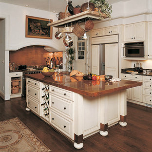 Inspiration for a traditional l-shaped kitchen pantry in Denver with an undermount sink, raised-panel cabinets, white cabinets, copper benchtops, brown splashback, stainless steel appliances, dark hardwood floors and with island.
