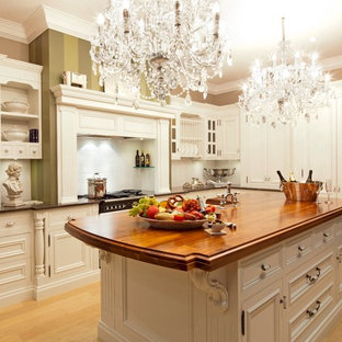 Example of a mid-sized classic galley light wood floor eat-in kitchen design in Sydney with beaded inset cabinets, white cabinets, wood countertops, white backsplash, an island and a farmhouse sink