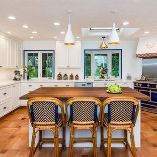 Medelhavsstil inredning av ett stort vit vitt kök, med en dubbel diskho, vita skåp, en köksö, integrerade vitvaror, klinkergolv i terrakotta, brunt golv, luckor med infälld panel och bänkskiva i koppar