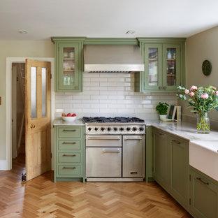 ロンドンの広いトラディショナルスタイルのおしゃれなキッチン (エプロンフロントシンク、シェーカースタイル扉のキャビネット、緑のキャビネット、珪岩カウンター、白いキッチンパネル、セラミックタイルのキッチンパネル、シルバーの調理設備、無垢フローリング、アイランドなし、茶色い床、マルチカラーのキッチンカウンター) の写真