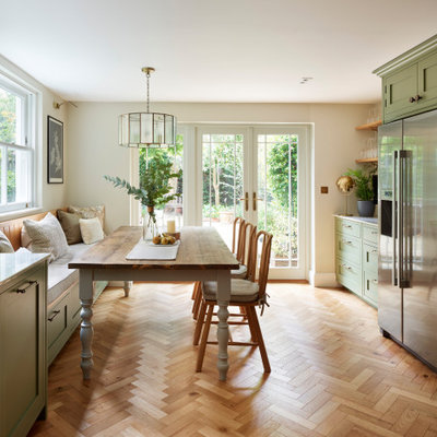 Example of a large classic u-shaped medium tone wood floor and brown floor eat-in kitchen design in London with a farmhouse sink, shaker cabinets, green cabinets, quartzite countertops, white backsplash, ceramic backsplash, stainless steel appliances, no island and multicolored countertops