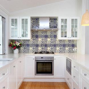 Inspiration för ett mellanstort vintage u-kök, med en undermonterad diskho, luckor med infälld panel, vita skåp, laminatbänkskiva, blått stänkskydd, stänkskydd i stenkakel, rostfria vitvaror och bambugolv