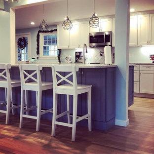 Offene, Zweizeilige, Mittelgroße Klassische Küche mit weißen Schränken, Küchenrückwand in Weiß, Rückwand aus Keramikfliesen, Küchengeräten aus Edelstahl, hellem Holzboden, Halbinsel, beigem Boden, grauer Arbeitsplatte und Schrankfronten mit vertiefter Füllung in Boston