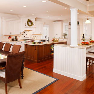 Mid-sized traditional eat-in kitchen photos - Mid-sized elegant u-shaped dark wood floor eat-in kitchen photo in New York with an undermount sink, white cabinets, granite countertops, white backsplash, subway tile backsplash, paneled appliances, an island and shaker cabinets