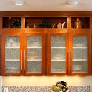 Example of a classic kitchen design in Portland with glass-front cabinets, medium tone wood cabinets and marble countertops