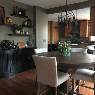 ニューヨークのヴィクトリアン調のおしゃれなキッチン (落し込みパネル扉のキャビネット、アンダーカウンターシンク、中間色木目調キャビネット、人工大理石カウンター、マルチカラーのキッチンパネル、ガラスタイルのキッチンパネル、シルバーの調理設備の、セラミックタイルの床、黒い床、黒いキッチンカウンター) の写真