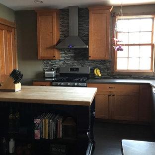 ニューヨークのヴィクトリアン調のおしゃれなキッチン (アンダーカウンターシンク、落し込みパネル扉のキャビネット、中間色木目調キャビネット、人工大理石カウンター、マルチカラーのキッチンパネル、ガラスタイルのキッチンパネル、シルバーの調理設備の、セラミックタイルの床、黒い床、黒いキッチンカウンター) の写真