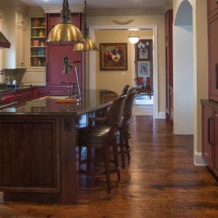 Klassische Küche in U-Form mit Landhausspüle, profilierten Schrankfronten, lila Schränken, bunter Rückwand, Elektrogeräten mit Frontblende, dunklem Holzboden, Kücheninsel, braunem Boden und schwarzer Arbeitsplatte in Los Angeles