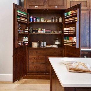 エセックスの大きいトラディショナルスタイルのおしゃれなキッチン (シェーカースタイル扉のキャビネット、濃色木目調キャビネット、淡色無垢フローリング、人工大理石カウンター、シルバーの調理設備の) の写真