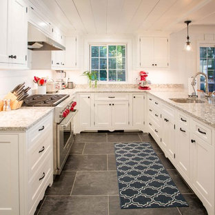 Traditional open concept kitchen designs - Open concept kitchen - traditional u-shaped black floor open concept kitchen idea in Grand Rapids with an undermount sink, shaker cabinets, white cabinets, stainless steel appliances and no island