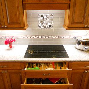 Große Klassische Wohnküche mit hellbraunen Holzschränken, Küchengeräten aus Edelstahl, Kücheninsel, Unterbauwaschbecken, profilierten Schrankfronten und Küchenrückwand in Beige in Dallas