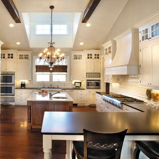 Inspiration for a large timeless u-shaped dark wood floor and brown floor kitchen remodel in Chicago with a farmhouse sink, recessed-panel cabinets, white cabinets, white backsplash, stainless steel appliances, two islands and subway tile backsplash
