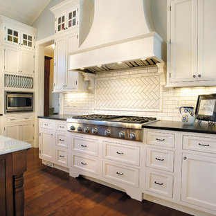 Example of a large classic u-shaped dark wood floor and brown floor enclosed kitchen design in Chicago with recessed-panel cabinets, white cabinets, white backsplash, stainless steel appliances, a farmhouse sink, an island and subway tile backsplash
