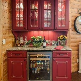 Foto de cocina en L, clásica, grande, abierta, con electrodomésticos de acero inoxidable, suelo de madera en tonos medios, una isla, fregadero sobremueble, armarios con paneles con relieve, puertas de armario rojas y salpicadero rojo