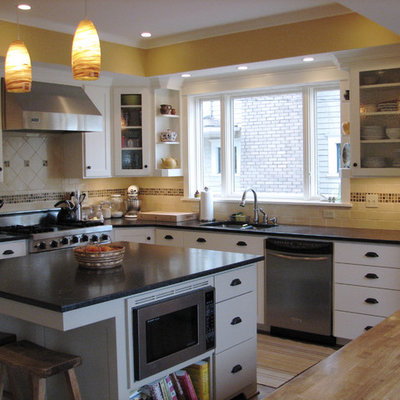 Example of a classic kitchen design in Other with white cabinets, multicolored backsplash and travertine backsplash