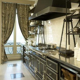 Inredning av ett klassiskt kök, med bänkskiva i rostfritt stål, vitt stänkskydd, stänkskydd i tunnelbanekakel och svarta vitvaror