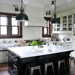 Выдающиеся фото от архитекторов и дизайнеров интерьера: кухня в классическом стиле с стеклянными фасадами, техникой из нержавеющей стали, раковиной в стиле кантри, белыми фасадами, мраморной столешницей, белым фартуком, фартуком из плитки кабанчик и белой столешницей